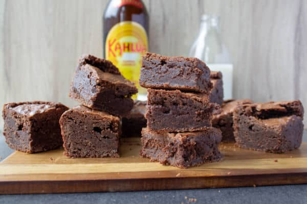 Stacks of Kahlua Brownies with a bottle of Kahlua in the background