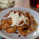 Croissant French Toast with Maple Bacon Whipped Cream on a white plate
