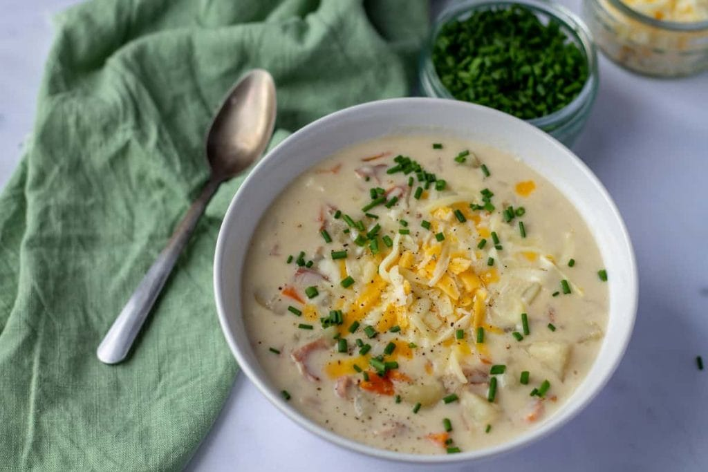 Ham & Potato Soup in a bowl with chives and green napkin