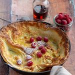 Dutch Baby with raspberries and powdered sugar