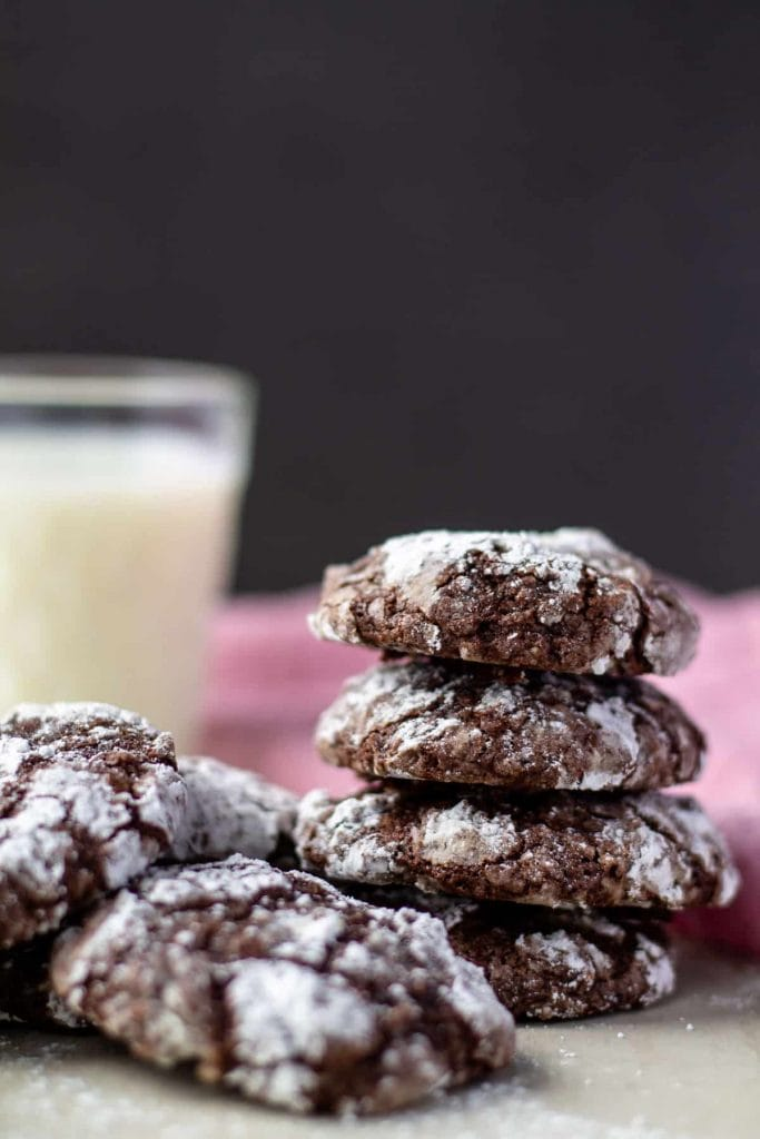 Chocolate Crinkle Cookies in a stack with milk