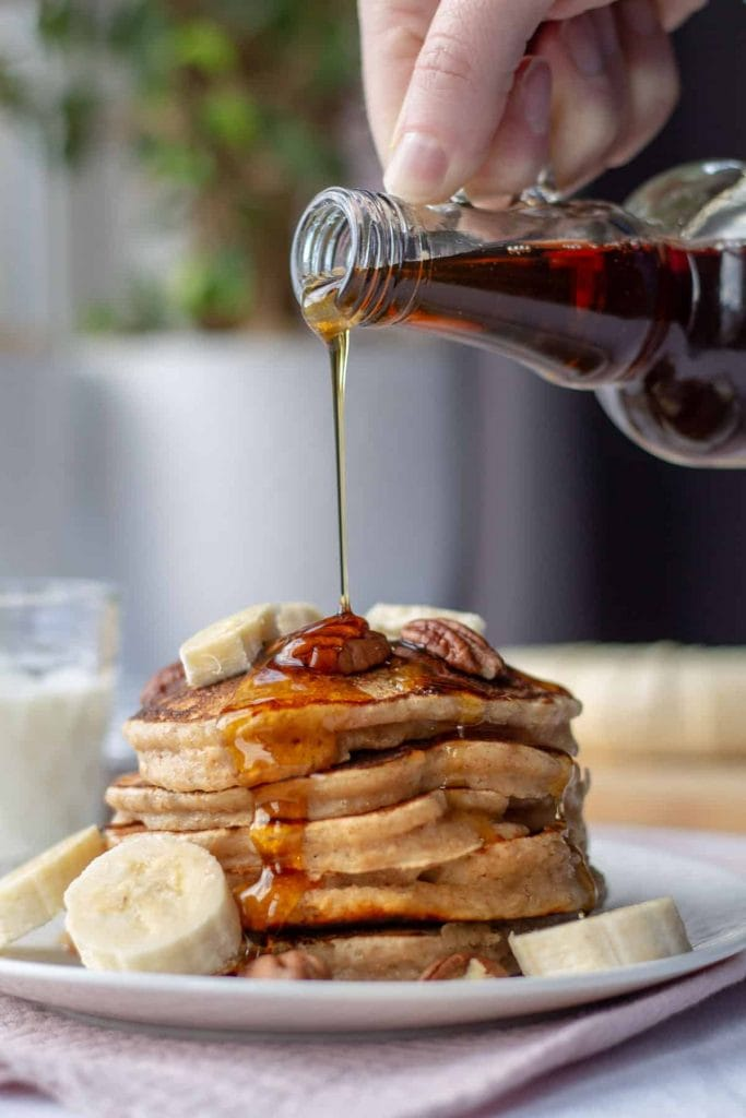 Whole Wheat Pancakes with pouring syrup