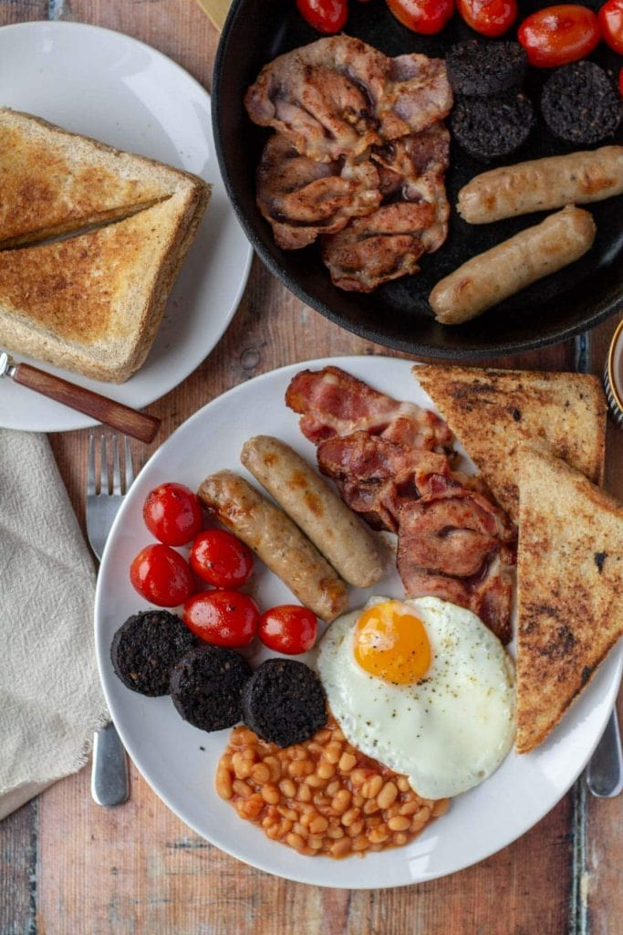 Full English Breakfast on a white plate with extras in skillet