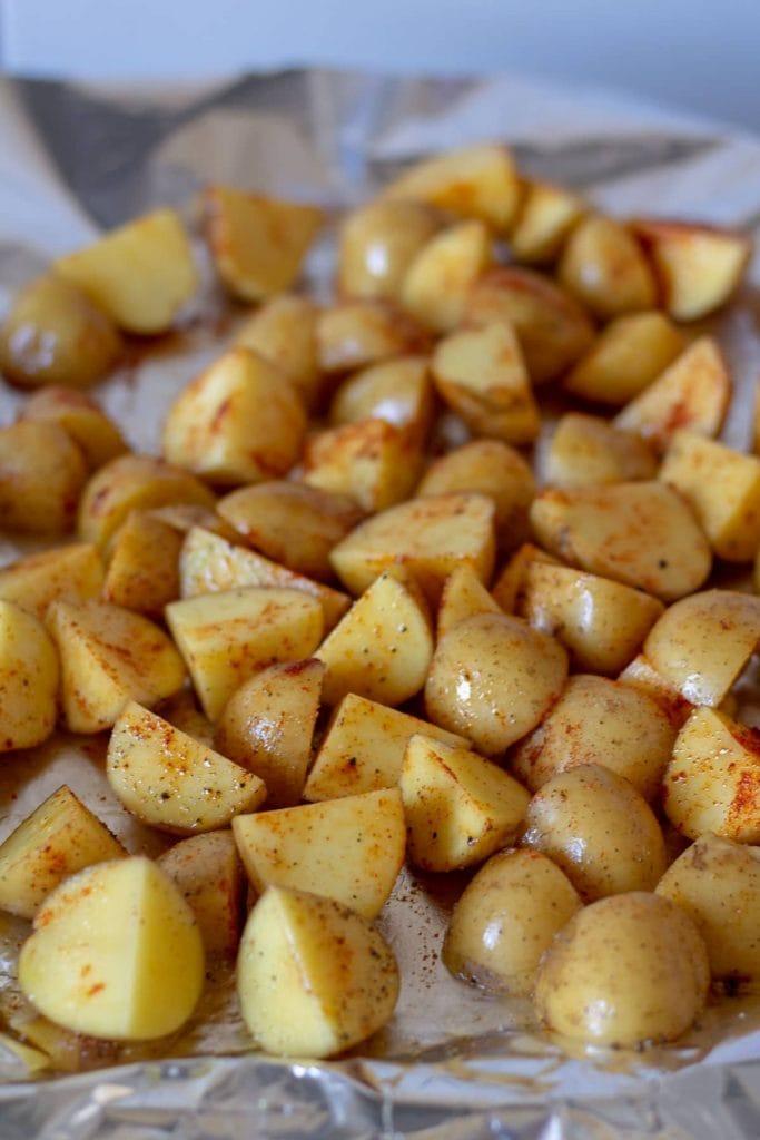 Chopped seasoned potatoes on foil
