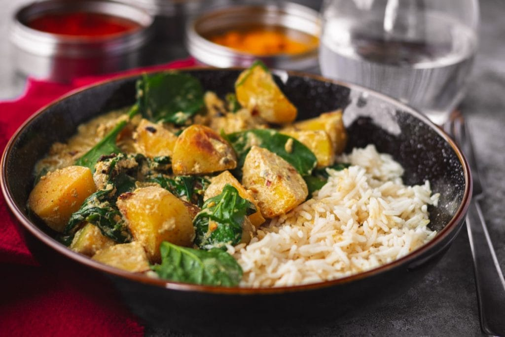 Potato & Spinach Curry in a black bowl