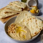 Easy Peanut Butter Hummus in a grey bowl with flatbread
