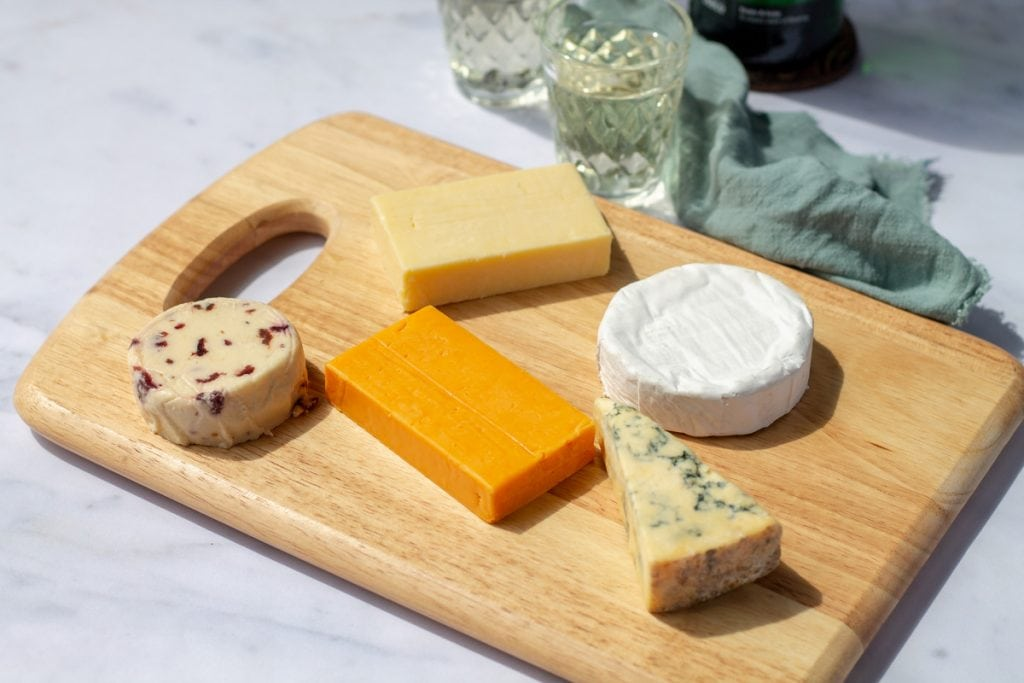 Five cheeses on a wooden board