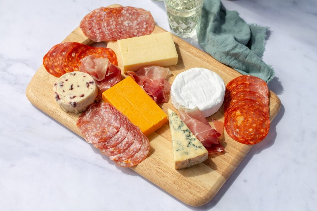 cheese and charcuterie on a wooden board