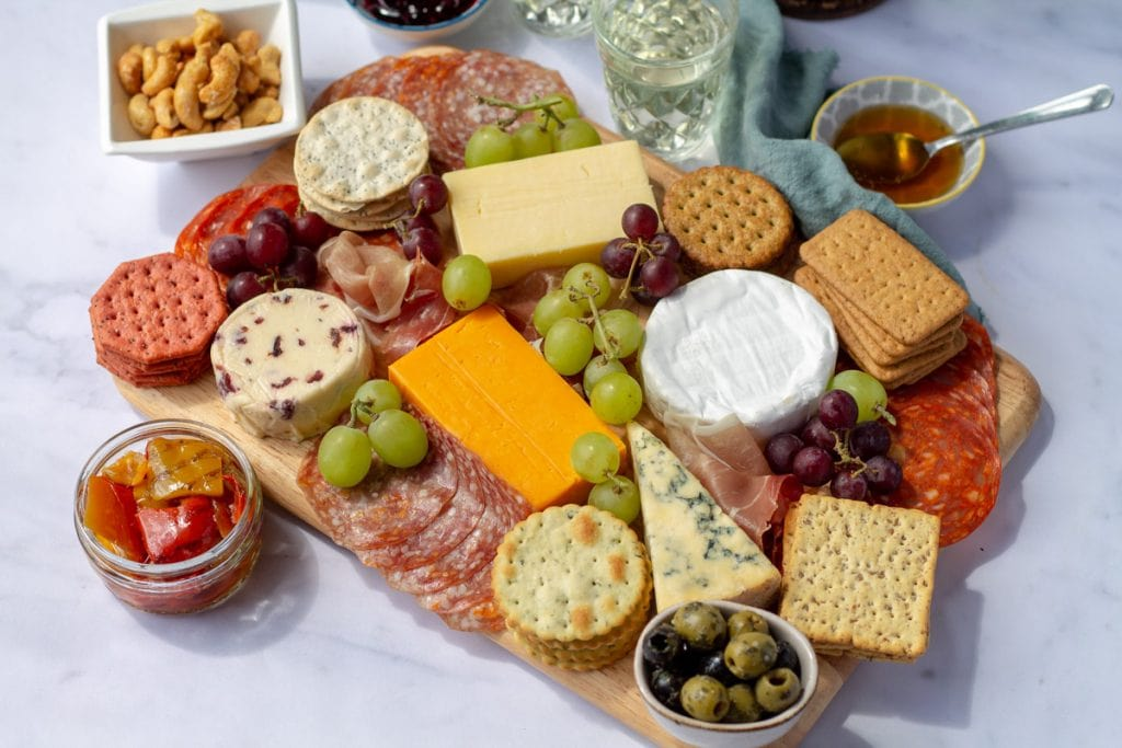 an epic cheeseboard with olives, nuts, and grapes