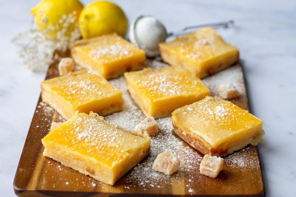 Lemon & Ginger Bars with crystalized ginger on a wooden board