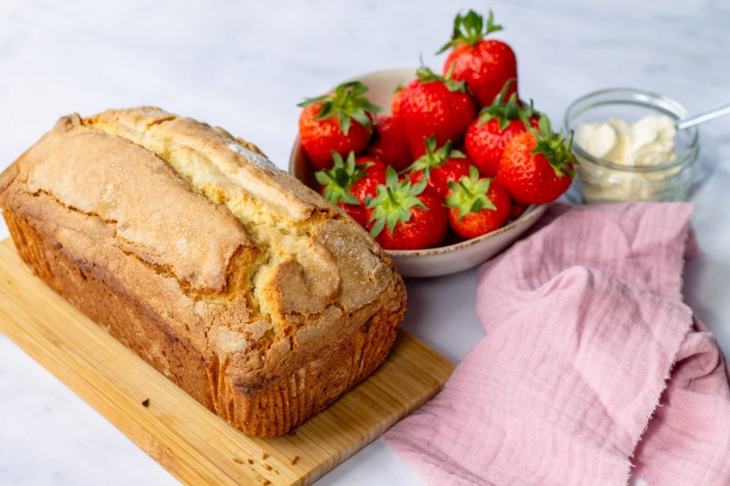 Madeira Cake whole loaf with bowl of strawberries, pink linen, and whipped cream