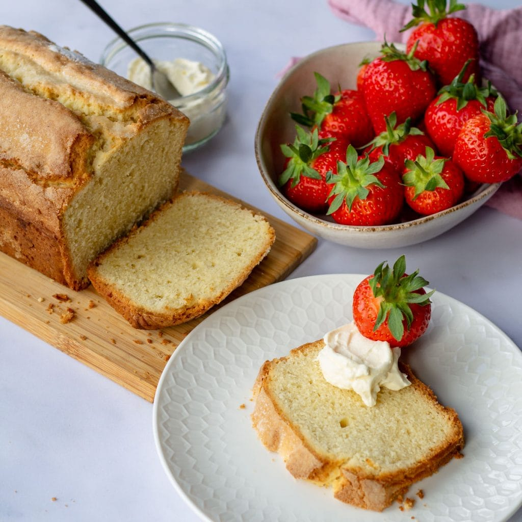 Madeira Cake sliced on a white plate with a strawberry