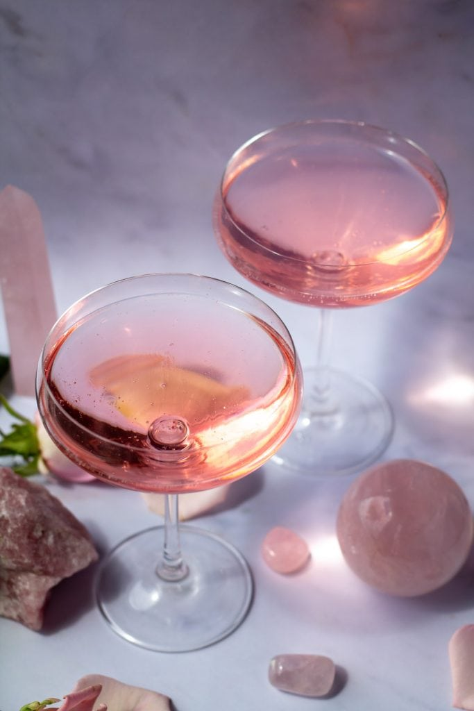 Rose Quartz Cocktail in coupe glasses surrounded by crystals
