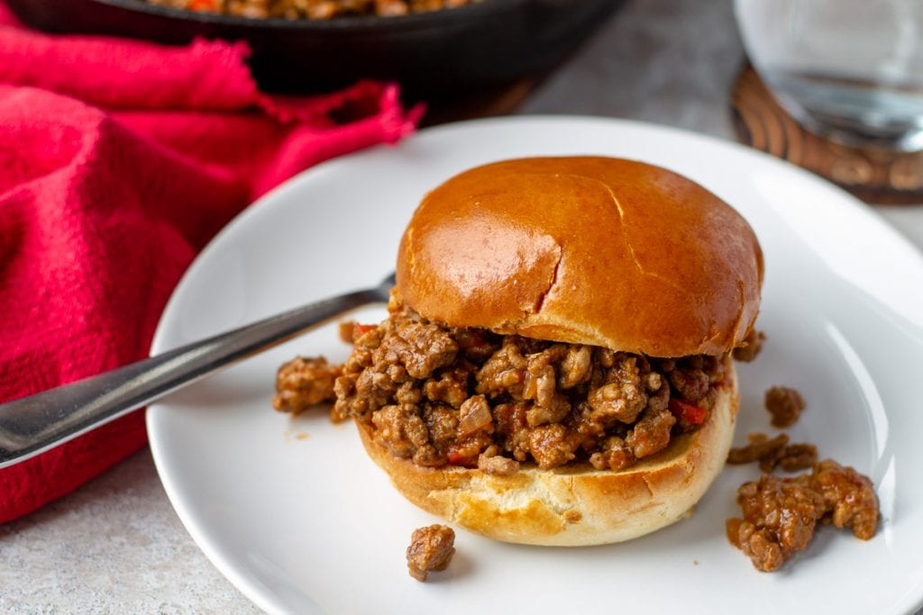 Sloppy joes on white plate with fork and red napkin