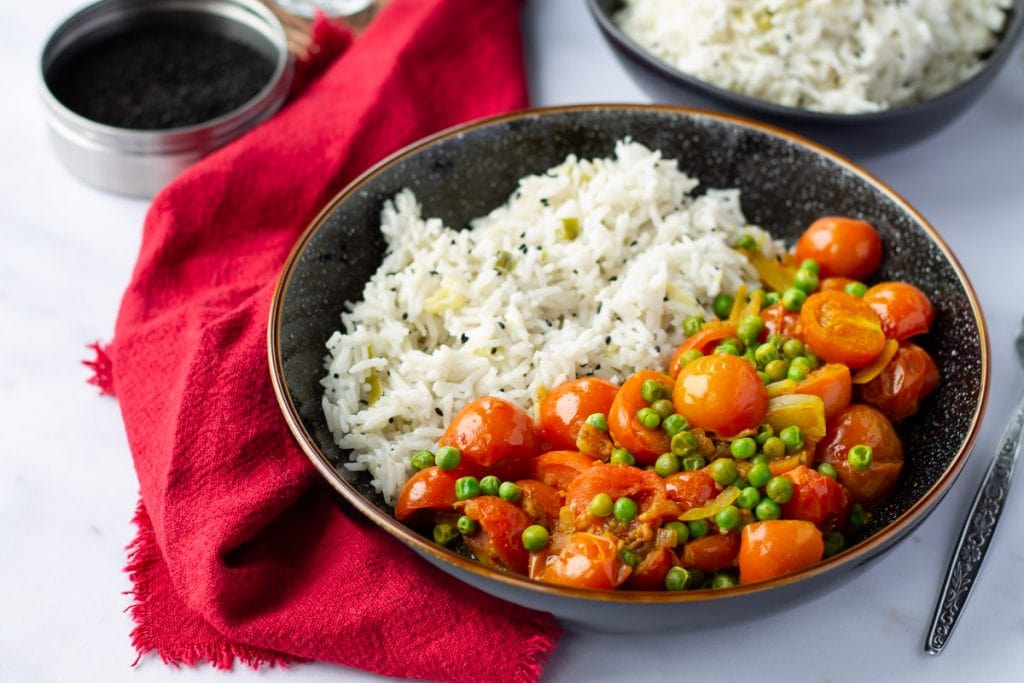 Vegan Tomato Curry with rice in a black bowl with red linen