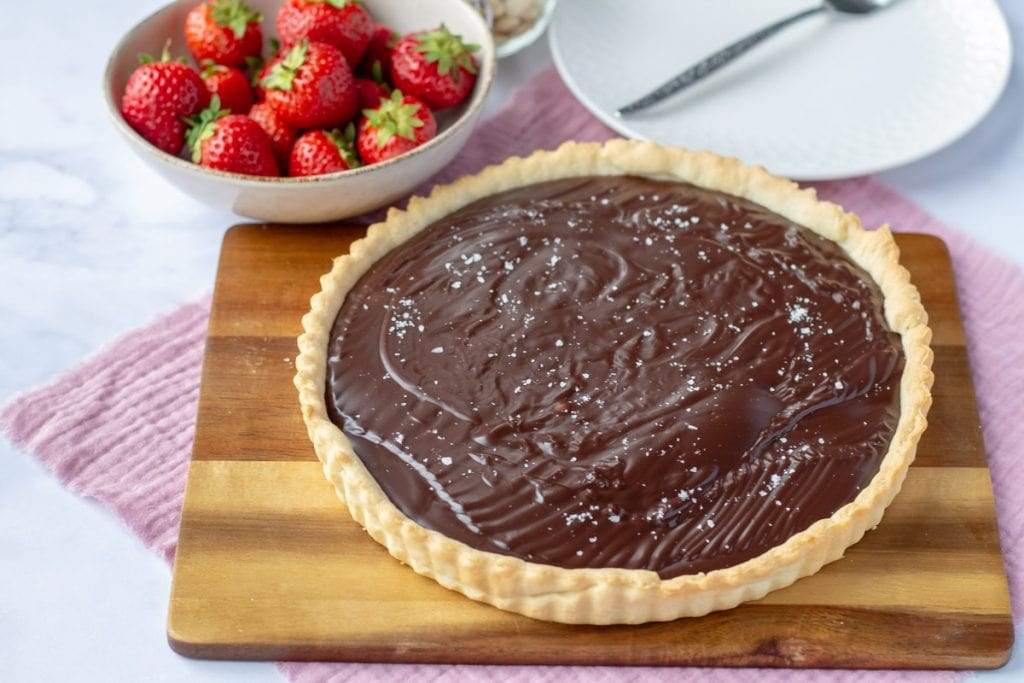 Chocolate Amaretto Tart whole with a bowl of strawberries